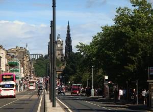 """这是一个美丽的苏格兰夏日。在爱丁堡王子大街上,你可以同时看到古希腊风格(远处左侧的圣女神殿""""残迹""""),哥特式建筑(司各特纪念碑),新古典主义建筑(Balmoral Hotel和苏格兰国家美术馆),和现代建筑。"""