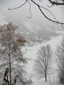大雪纷飞,在Salisbury Crags 上形成一片白色的迷雾。有人背着看上去像是雪橇的东西走过。