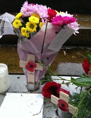 """这束花上的纸条上写着:""""献给我们的叔叔罗伯特·摩尔,1918年10月2日阵亡。对他的记忆永远留在我们心中。"""""""